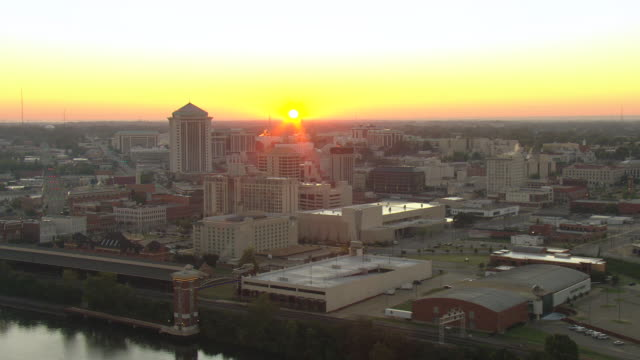 WS AERIAL View of sunrise over city buildings / Montgomery, Alabama, United States