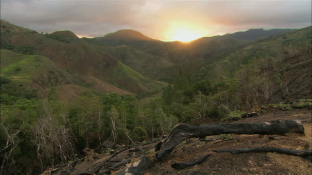 vidéos et rushes de ws pan view of sunrise over mountains / new caledonian - french overseas territory
