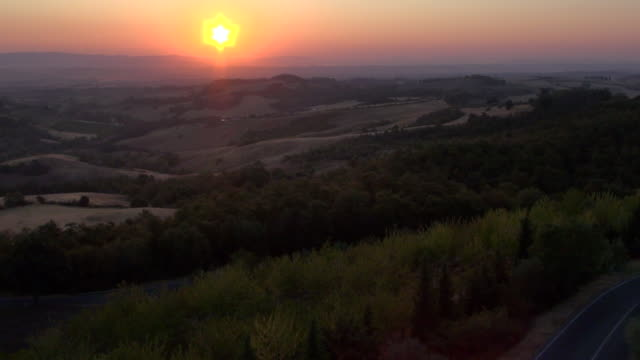 vidéos et rushes de ws aerial view of sunrise over tuscan hills in crete senesi / pienza, tuscany, italy - toscane