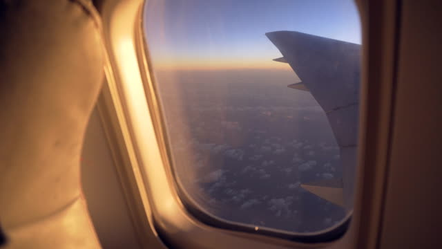 View of sunrise through airplanes window during flight