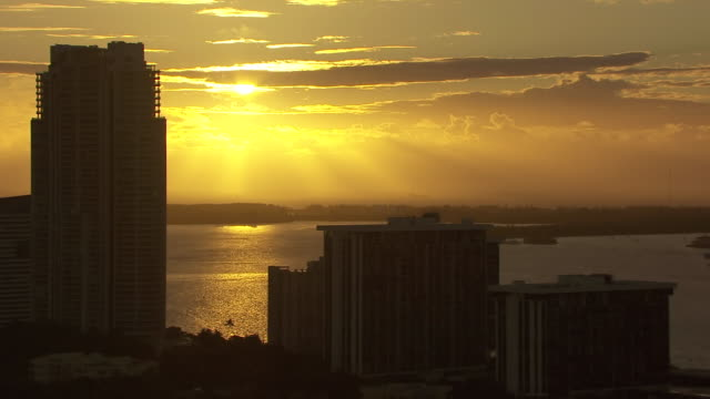 WS AERIAL View of sunrise through clouds and sun going in back of buildings / Miami, Florida, United States