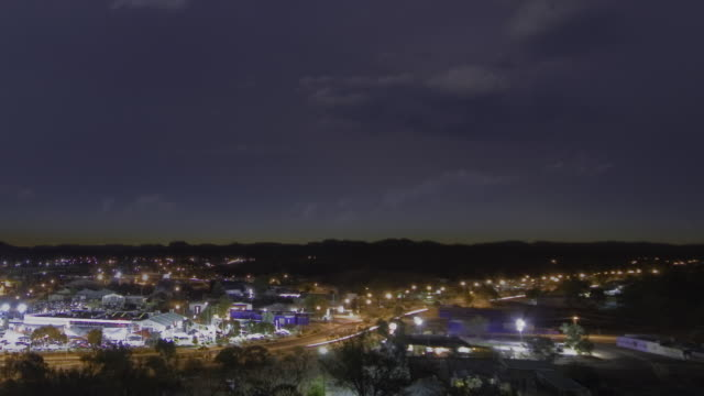 ws zo t/l view of sunset behind alice springs at dusk, as night falls thunderstorm with lightning flashes over the city / alice springs, northern territory, australia. - town stock videos & royalty-free footage