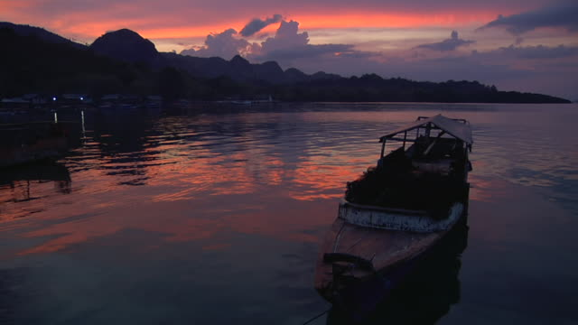 WS View of sunset behind mountains with port and canoe / Rinca Island,  Indonesia