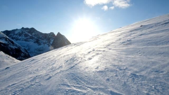 blick auf den sonnenuntergang auf verschneiten hügel in schneesturm am ryten berg, norwegen - gebirgskamm stock-videos und b-roll-filmmaterial