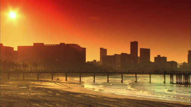 ws pan view of sunset over durban city and beach / durban, kwazulu-natal, south africa - durban stock videos and b-roll footage
