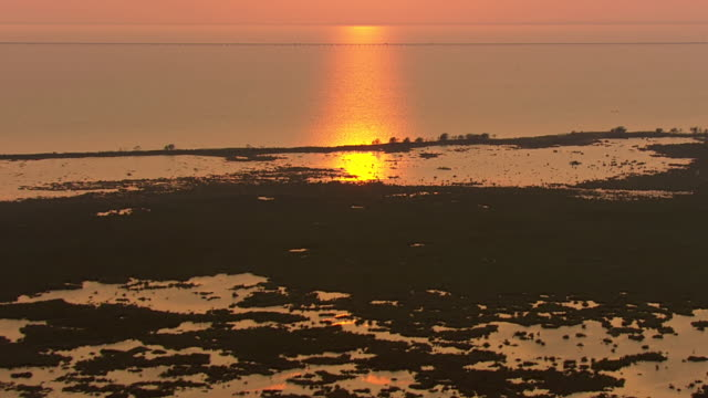 View of sunset over Lake Pontchartrain near flooded area / United States