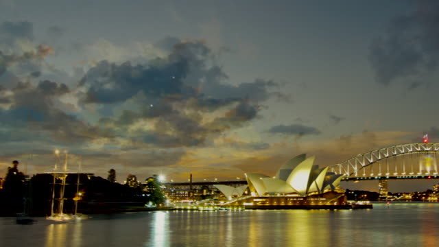 ws pan t/l view of sunset over opera house / sydney, australia - オペラ座点の映像素材/bロール