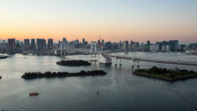 WS T/L View of sunset over rainbow bridge with city skyline / Tokyo, Japan