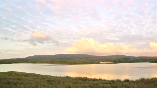 ws pan view of sunset over scottish loch with clouds / skye island, scotland, united kingdom - 2k resolution stock videos and b-roll footage