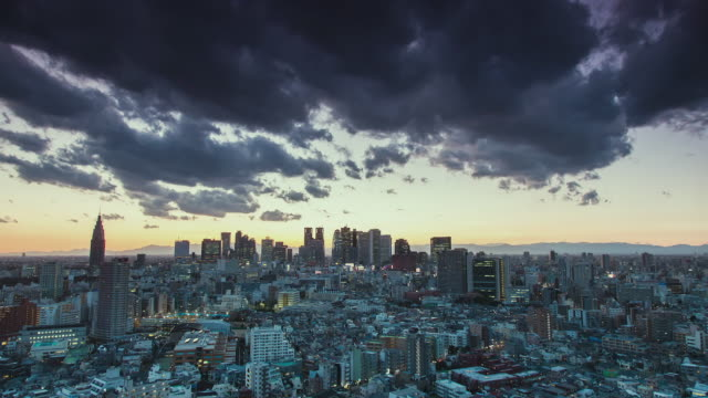 ws t/l view of sunset over shinjuku business and shopping area with dark clouds moving in sky / tokyo, japan - tokyo japan stock videos & royalty-free footage