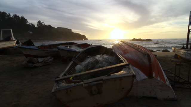 ms pan view of sunsets on beach with boats / horcon, chile - wiese stock videos & royalty-free footage
