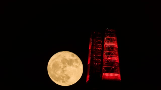 View of Supermoon passing by Lotte World Tower (One of the tallest buildings in Korea) at night