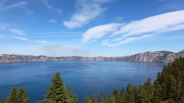 ws pan view of surface of crater lake through the forest / klamath county, oregon, united states - crater lake oregon stock videos & royalty-free footage