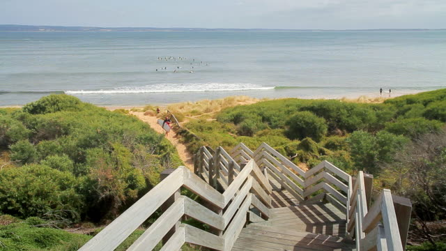 ws view of surfer and his daughter climb steps from picturesque cat bay on westernport bay / phillip island, victoria, australia  - leisure activity stock videos & royalty-free footage