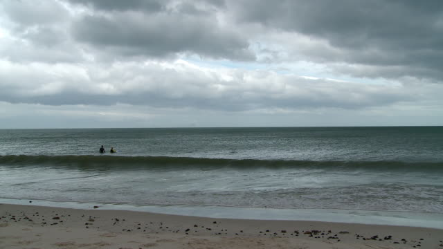 ws view of surfers waiting for wave / western cape, south africa - distant stock videos and b-roll footage