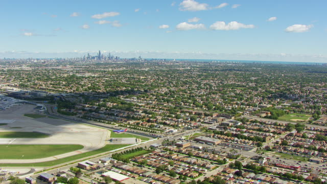 ws aerial pov view of surrounding neighbourhoods to downtown skyline in background / chicago, cook county, illinois, united states - blickwinkel aufnahme stock-videos und b-roll-filmmaterial