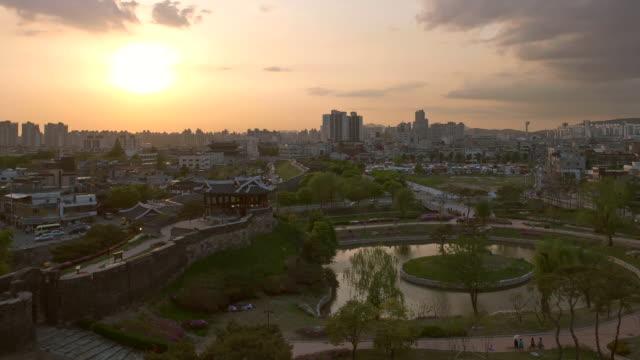 ws t/l zi view of suwon hwaseong castle behind suwon cityscape / suwon, gyeonggi-do, south korea - suwon stock videos and b-roll footage