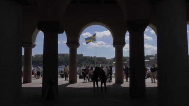view of swedish flag and people beneath town hall tower, stockholm, sweden, scandinavia, europe - svezia video stock e b–roll