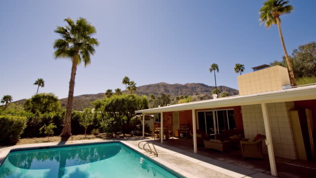 ws t/l view of swimming pool and backyard of ranch style home / palm springs, california, usa - palm springs california pool stock videos & royalty-free footage