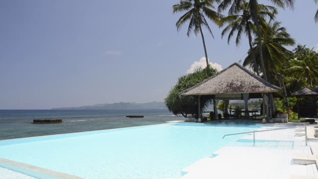 vidéos et rushes de ms view of swimming pool in front of beach at asia / candi dasa, bali, indonesia - lockdown