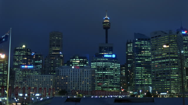 View of Sydney Tower and Sydney central business district skyline from Darling Harbour at night / Sydney, Australia