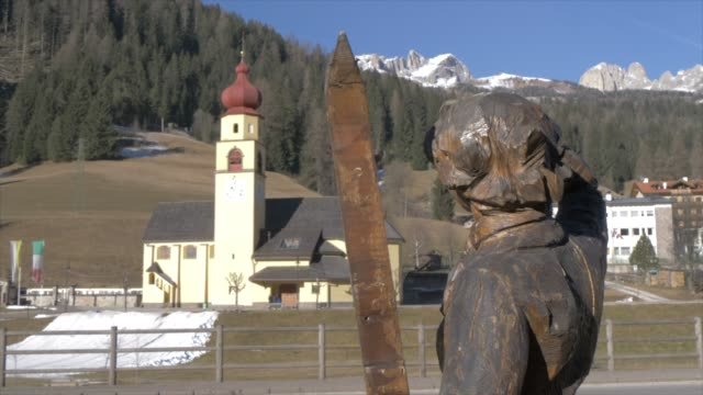 view of symbolic skier and church in soraga on sunny day in winter, province of trento, italian dolomites, italy, europe - religion stock-videos und b-roll-filmmaterial
