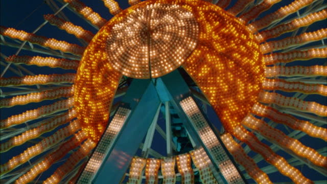ms view of tall ferris wheel rolling with many decorative lights at amusement park - glühbirne stock-videos und b-roll-filmmaterial