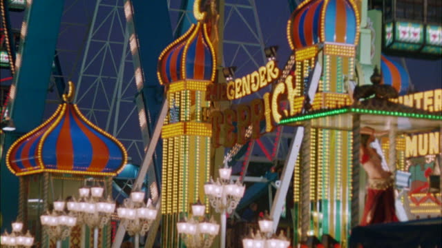 ms tu view of tall ferris wheel rolling with many decorative lights at amusement park - anno 1983 video stock e b–roll