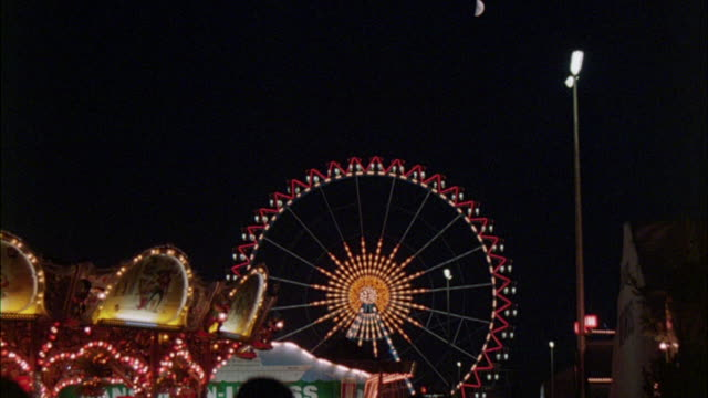 ws view of tall ferris wheel rolling with many decorative lights at amusement park - 1982 stock videos & royalty-free footage
