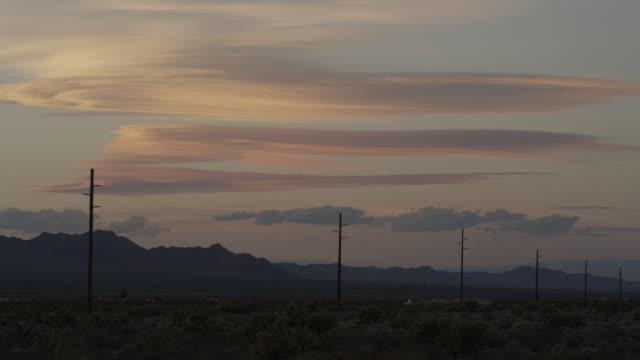 ws view of telephone poles along highway with mountains at dusk / kingman, arizona, united states - kingman arizona stock videos & royalty-free footage