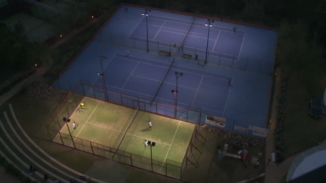 ms view of tennis and paddle court at night / malaga, andalusia, spain - sportplatz stock-videos und b-roll-filmmaterial