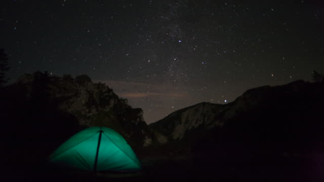 vidéos et rushes de ms t/l view of tent in alpine mountains underneath starry sky at night to dawn / bayrischzell, bavaria, germany - bavière