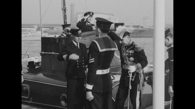 stockvideo's en b-roll-footage met view of thames river with boats on it / barge bearing portugal's president francisco craveiro lopes arrives at pier naval officer and two sailors... - militair uniform