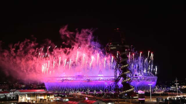view of the 2012 london olympic opening ceremony from a nearby vantage point / the olympic stadium and the arcelor mital orbit tower are illuminated... - 2012年ロンドン夏季オリンピック点の映像素材/bロール