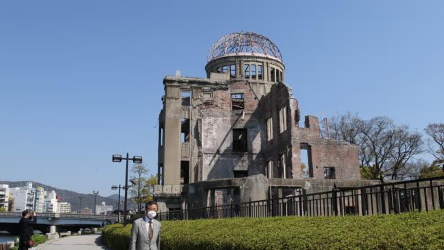 vidéos et rushes de view of the a-bomb dome at the hiroshima peace memorial and visitors passing by. - arme de destruction massive