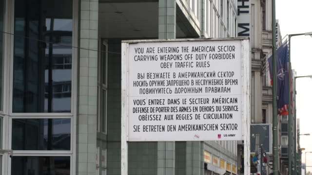 View of the actual Berlin wall and border memorial at Checkpoint Charlie with a close up of the sign You are entering the american sector Carrying...