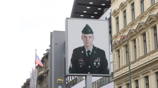 A view of the actual Berlin wall and border memorial at Checkpoint Charlie wit a close up of a portrait of an american soldier the bestknown Berlin...