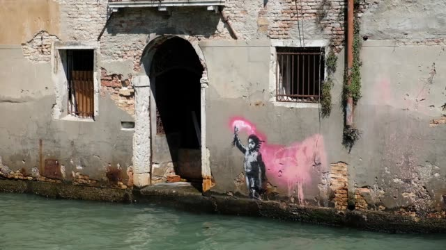 a view of the alleged artistic work of the american street artist banksy just called the shipwrecked child who appeared on the outer wall of a house... - バンクシー点の映像素材/bロール