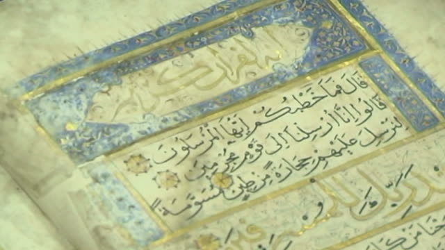 view of the arabic calligraphy and rich decorative border in an illuminated antique qoran in the marachi najafi library collection. - capital letter stock videos & royalty-free footage