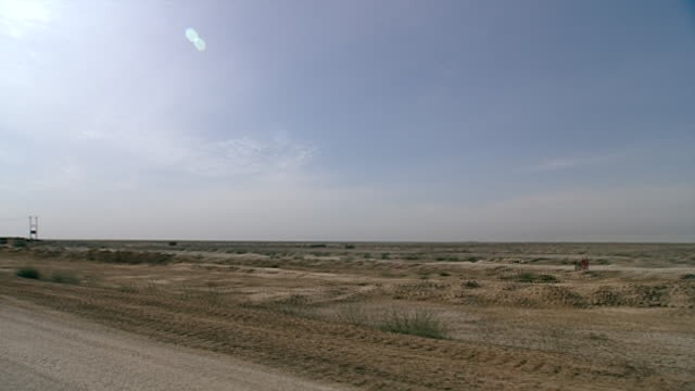 view of the arid landscape through a traveling car window stretching out into the iraqi desert south of baghdad towards warka. - arid stock videos & royalty-free footage