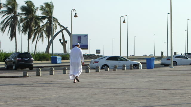 view of the back of a saudi man in a white thobe walking on the corniche in jeddah - dish dash stock videos & royalty-free footage