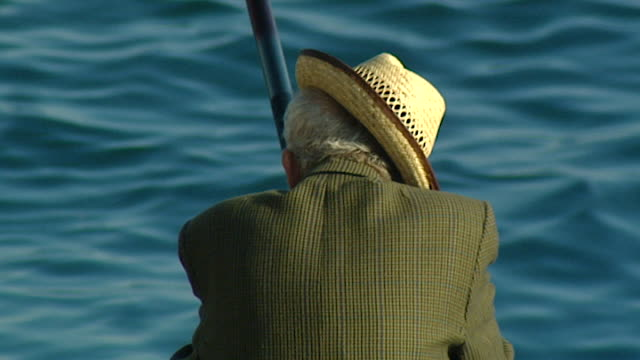 view of the back of an old man, wearing a straw hat at a jaunty angle, fishing in the mediterranean, on the corniche in ain mreisse, beirut. - straw hat stock videos & royalty-free footage