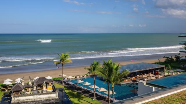 view of the beach in front of alila seminyak bali resort in bali, indonesia - freibad stock-videos und b-roll-filmmaterial