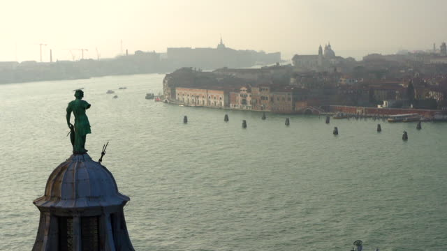 vidéos et rushes de view of the bronze statue on a tower and a seaside structures in venice, italy - surface aquatique