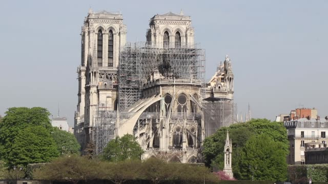 view of the cathedral with the seine.a fire broke out on monday afternoon and quickly spread across the building, causing the famous spire to... - spire stock videos & royalty-free footage