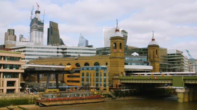 view of the city of london skyline as a train enters cannon street station - bassa marea video stock e b–roll