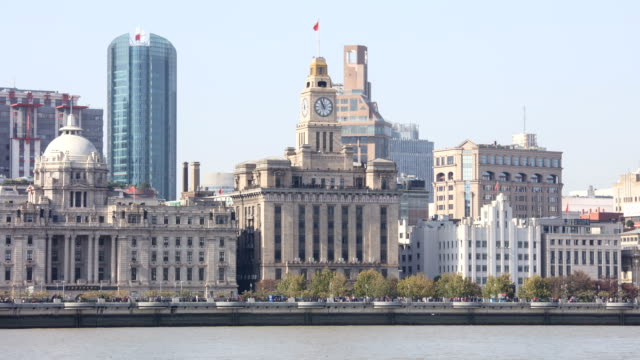 view of the clock tower and buildings on the huangpu river at daytime in the bund(waitan) area, in shanghai, china - the bund stock videos & royalty-free footage