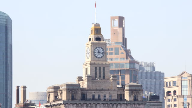 view of the clock tower at daytime in the bund(waitan) area, shanghai, china - turmuhr stock-videos und b-roll-filmmaterial