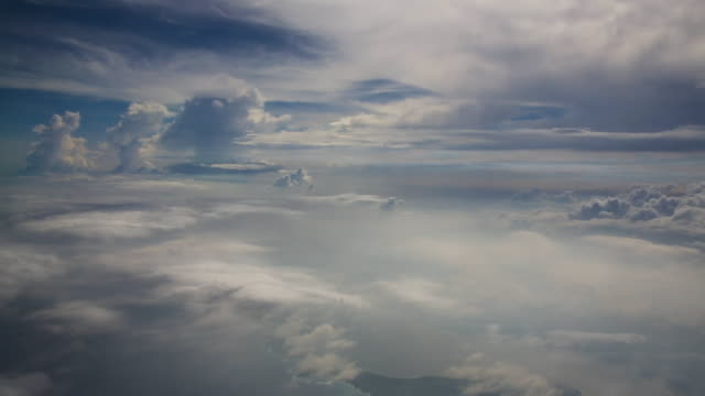 vídeos de stock, filmes e b-roll de view of the clouds and blue sky from an airplane - acima