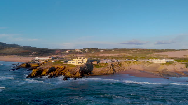 view of the crismina beach and guincho beach with the sintra mountain in the background - カスカイス点の映像素材/bロール